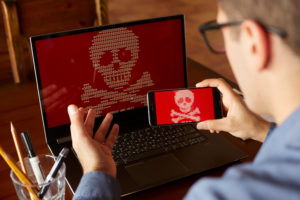 Man sits near laptop with phone blocked and encrypted by ransomware spyware asking for money. Laptop and smartphone infected by virus. Scary red skull crossbones on screen. Cyber security theme.